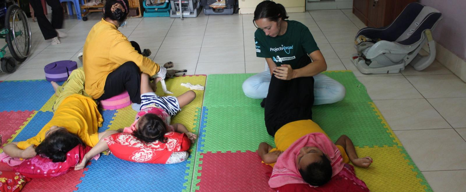 A Physiotherapy intern works with a young patient at a rehabilitation centre in Cambodia.